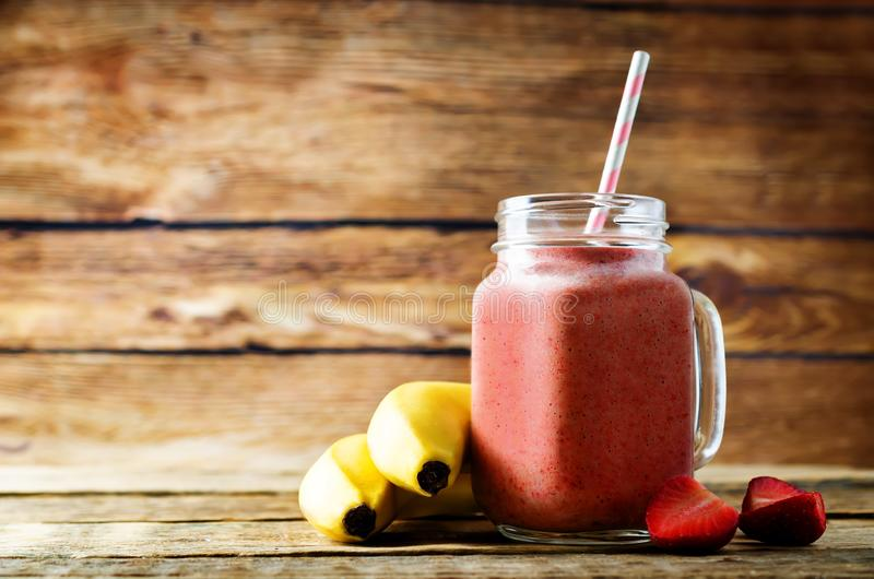 Strawberry banana smoothie on a dark wood background. Toning. selective Focus royalty free stock image