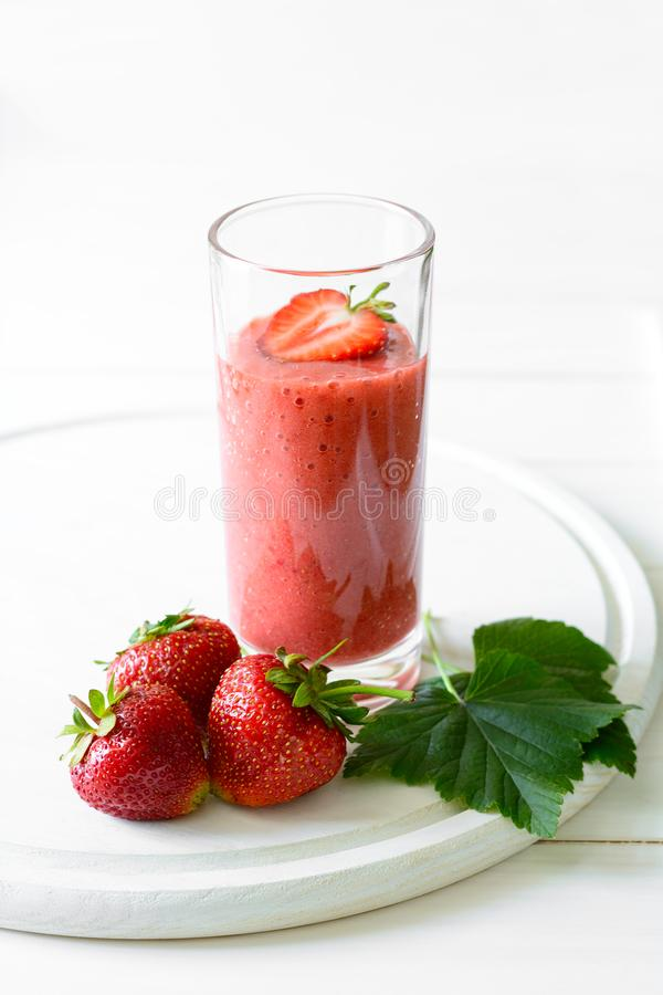 Strawberry and banana smoothie glass on white wooden background. Detox and healthy eating concept royalty free stock image