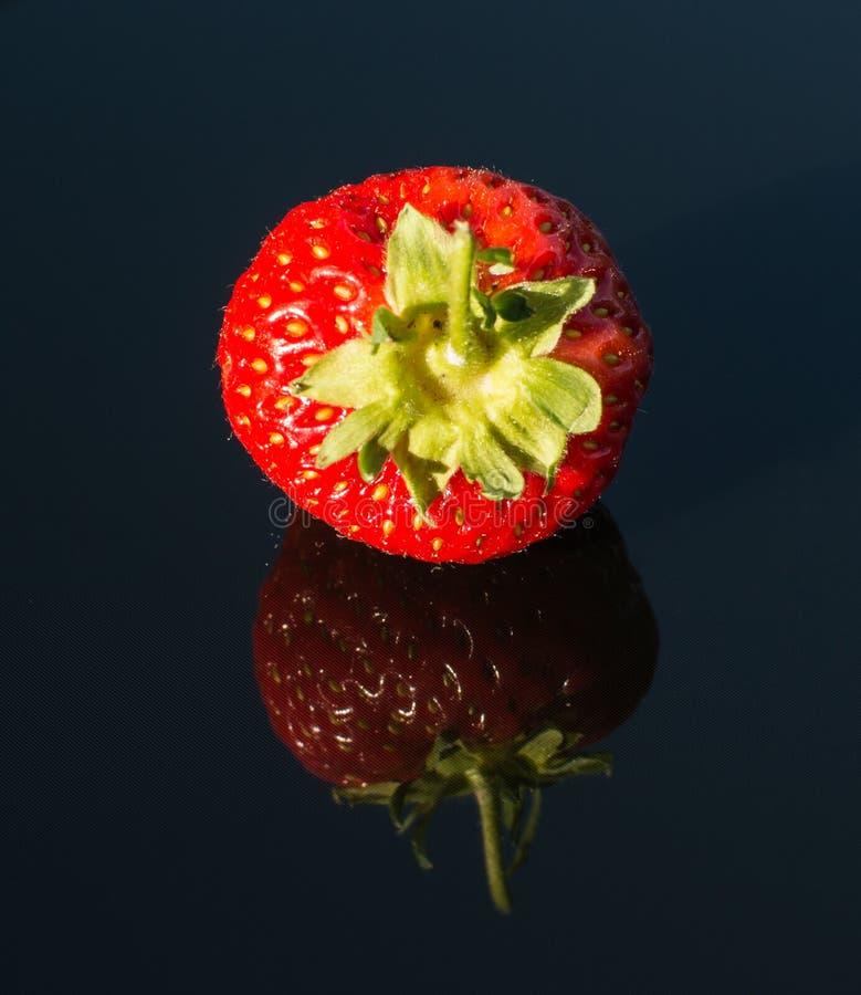 Strawberry on black glass 3. Double strawberry on black glass stock photos