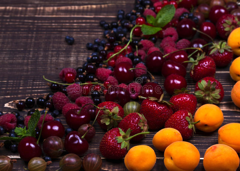 Strawberry, blueberry, blackberry, raspberry, cherry, apricots, gooseberry and currant. On dark wooden background royalty free stock photography