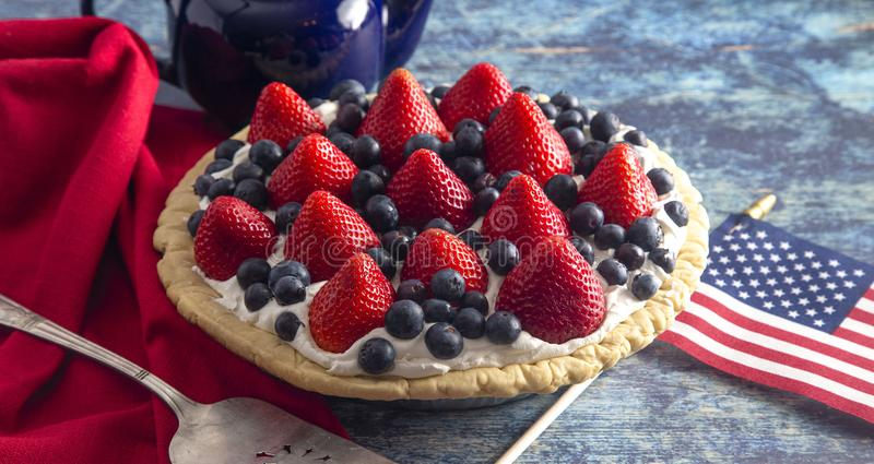 A Strawberry and Blueberry Fresh Summer Pie on a Distressed Blue Wooden Table. Strawberry and Blueberry Fresh Summer Pie on a Distressed Blue Wooden Table stock images