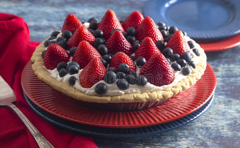 A Strawberry and Blueberry Fresh Summer Pie on a Distressed Blue Wooden Table. Strawberry and Blueberry Fresh Summer Pie on a Distressed Blue Wooden Table royalty free stock image