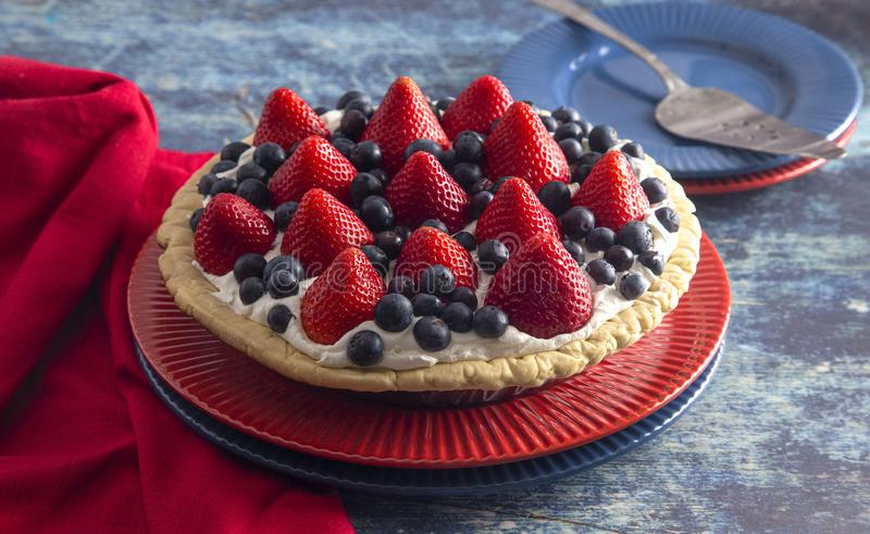A Strawberry and Blueberry Fresh Summer Pie on a Distressed Blue Wooden Table. Strawberry and Blueberry Fresh Summer Pie on a Distressed Blue Wooden Table stock photo