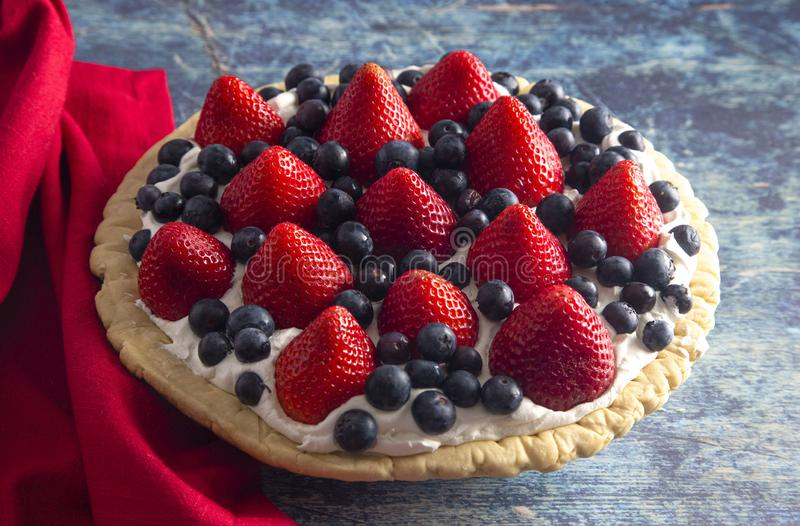 A Strawberry and Blueberry Fresh Summer Pie on a Distressed Blue Wooden Table. Strawberry and Blueberry Fresh Summer Pie on a Distressed Blue Wooden Table royalty free stock photography