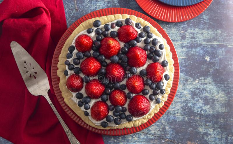 A Strawberry and Blueberry Fresh Summer Pie on a Distressed Blue Wooden Table. Strawberry and Blueberry Fresh Summer Pie on a Distressed Blue Wooden Table stock photos
