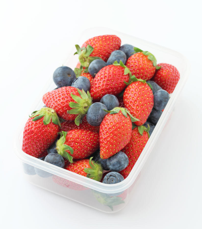 Strawberry and blueberry mix in plastic container. Over white background royalty free stock photography