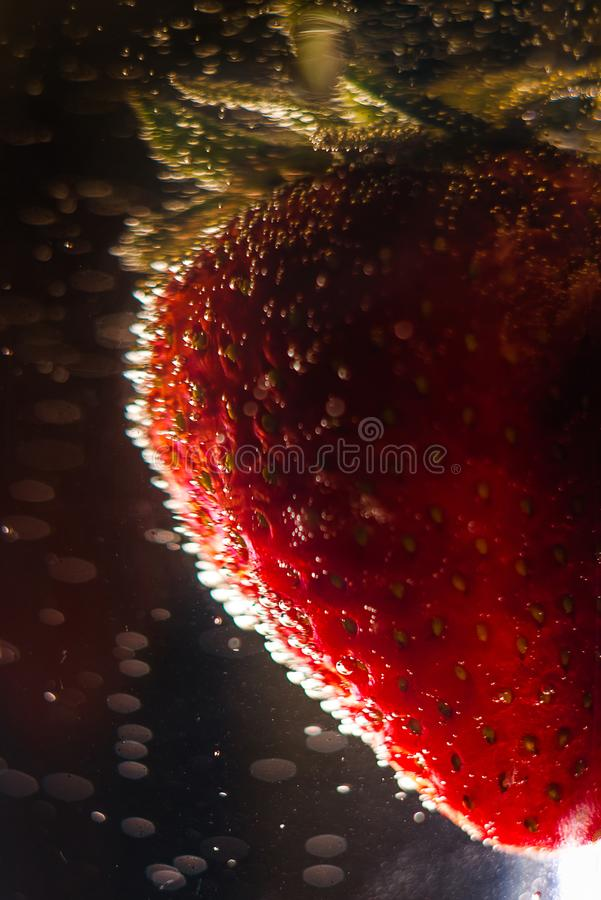 Strawberry in bubbles of champagne. Delicious strawberries in refreshing bubbles of champagne. A beautiful berry royalty free stock image