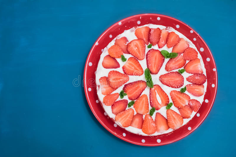 Strawberry cake with sour cream on a blue background top view royalty free stock photography