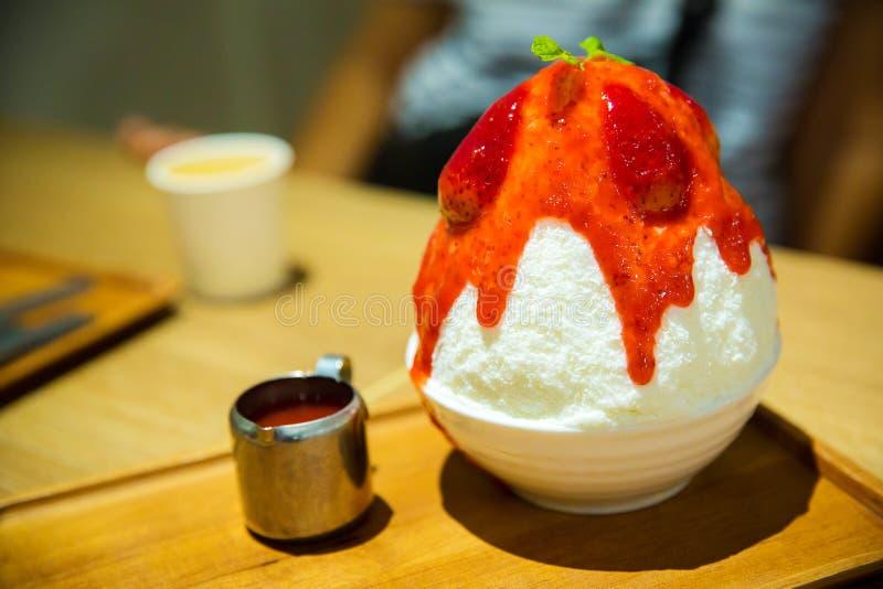 Strawberry cheesecake bingsu. Korean shaved milk ice topped by fresh strawberry and strawberry sauce. trendy Korean dessert . stock images
