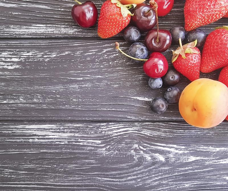 Strawberry, cherry, blueberry, frame harvest delicious apricot on a wooden background stock photos