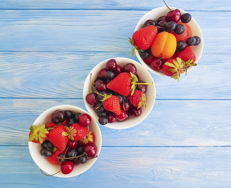 Strawberry, cherry, blueberry, organic plate vitamin harvest apricot on a wooden background stock photography