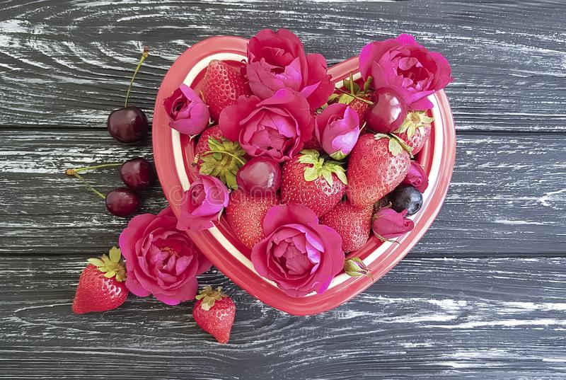 Strawberry, cherry, blueberry natural fruit plate heart, fresh vintage appetizing flower rose on a black wooden background stock photo