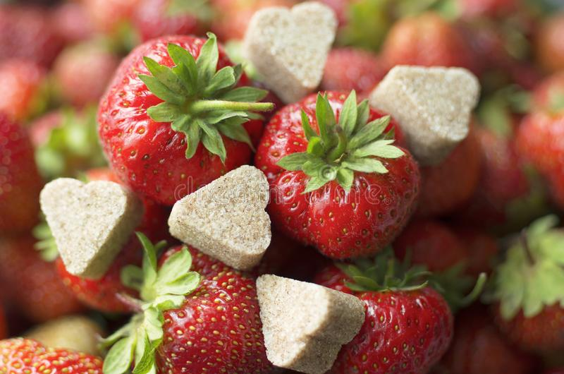 Strawberry with chunks of cinnamon sugar in the shape of hearts royalty free stock image