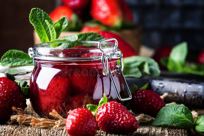 Strawberry confiture with whole berries, vintage wooden background, selective focus royalty free stock photo