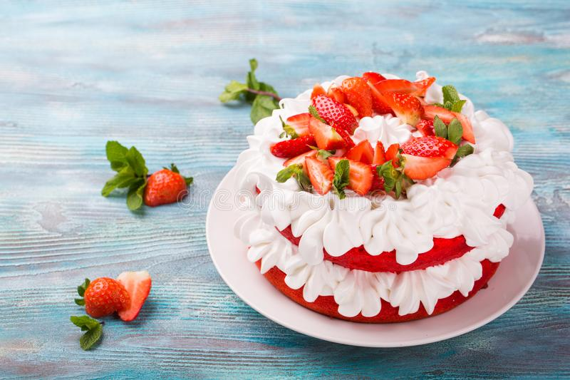 Strawberry and cream sponge cake. Homemade summer dessert on blue wooden table royalty free stock photo