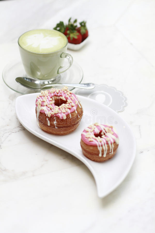 Strawberry croissant donut and a cup of milk green tea stock photo