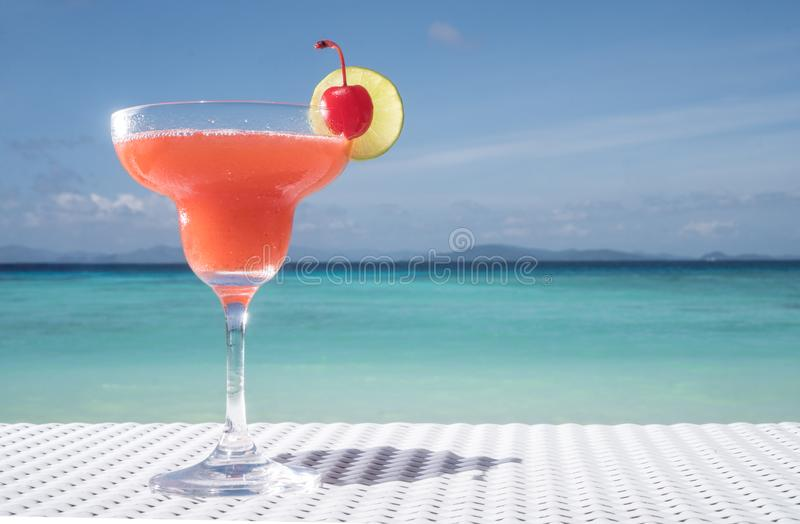 Strawberry Daiquiri cocktail on the table at the beach restaurant. Strawberry Daiquiri cocktail on the white rattan table at the beach restaurant with beautiful royalty free stock photo