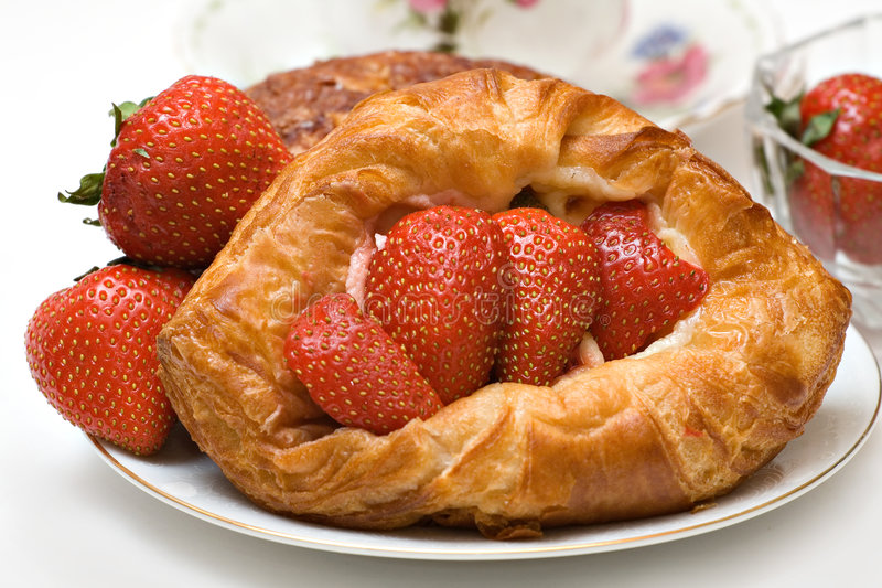 Strawberry Danish. Variety of pastries featuring a strawberry danish - fresh strawberries cup saucer visible stock photography