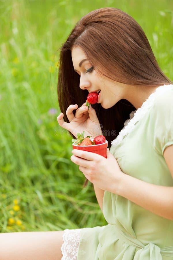 Strawberry desire. Girl enjoying strawberries in the park stock photos
