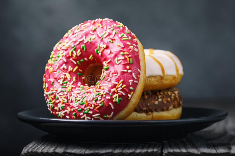 Strawberry donut in a black ceramic plate on a wooden table stock image