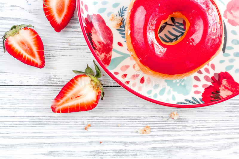 Strawberry donut on plate flat lay wooden background top view mock up stock photos
