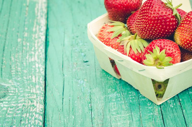 Strawberry. Fresh berries of strawberry on wooden green table/Selective focus. Strawberry in small basket on natural wooden royalty free stock photo