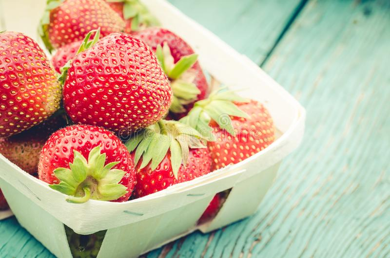 Strawberry. Fresh berries of strawberry on wooden green table/Strawberry in small basket on natural wooden background royalty free stock images