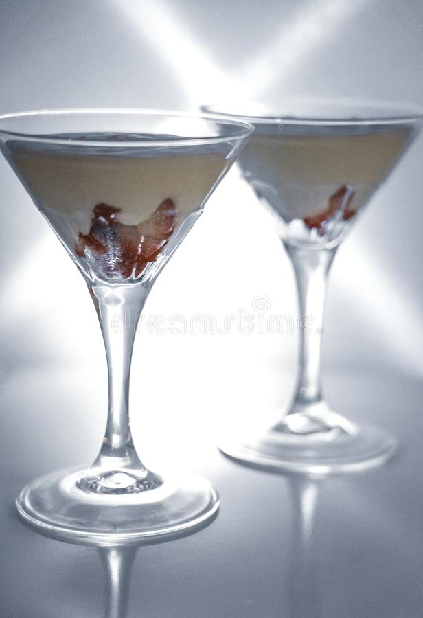 Strawberry fromage dessert. In coctail glasses and lighted with artificial light. Dessert and coctail concept stock image