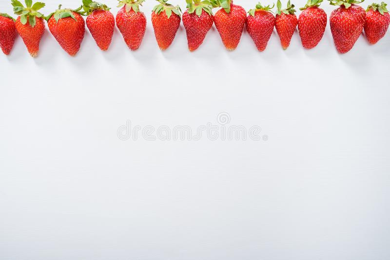 strawberry fruits in a row on white wood table background stock images