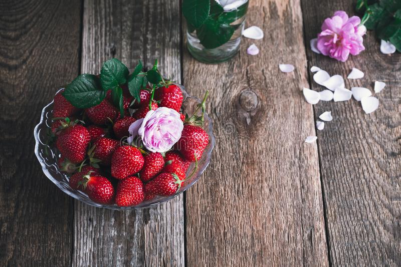 Strawberry in glass bowl, high angle view. Strawberry in glass bowl on rustic wooden table, still life with berries and pink roses, plant based food, high angle stock photos