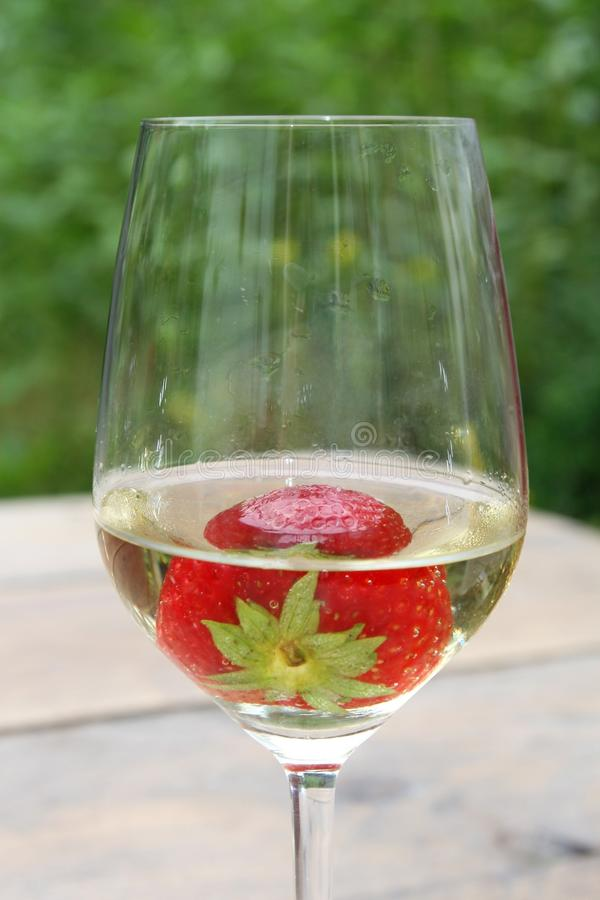 Strawberry in a glass of biological white wine. Strawberry in a cool glass of white wine feels like summertime. For various celebrations royalty free stock photo