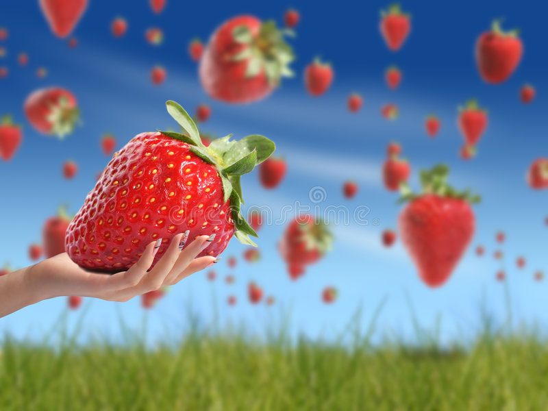 Strawberry in hand. Strawberry rain concept. Green grass and blue sky on the background