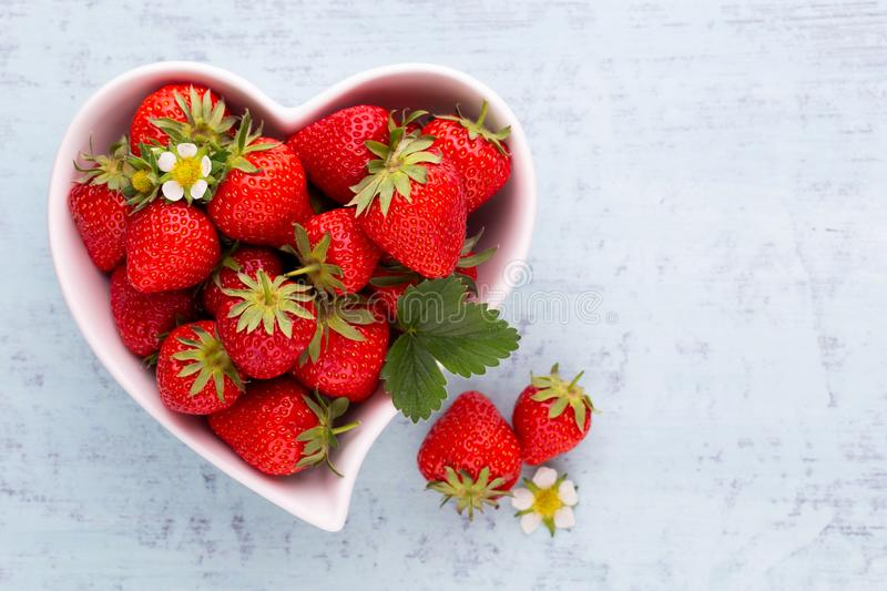 Strawberry heart. Fresh strawberries in plate on white wooden table. Top view, copy space stock photos