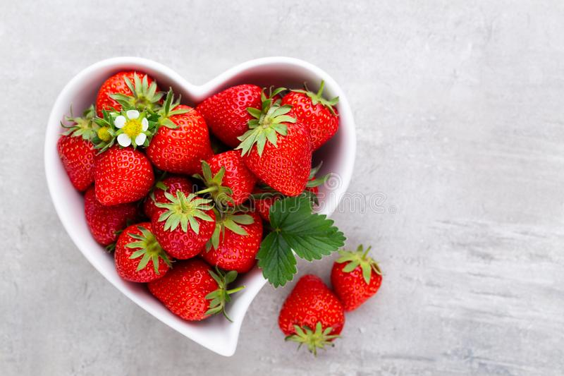 Strawberry heart. Fresh strawberries in plate on white wooden table. Top view, copy space stock image
