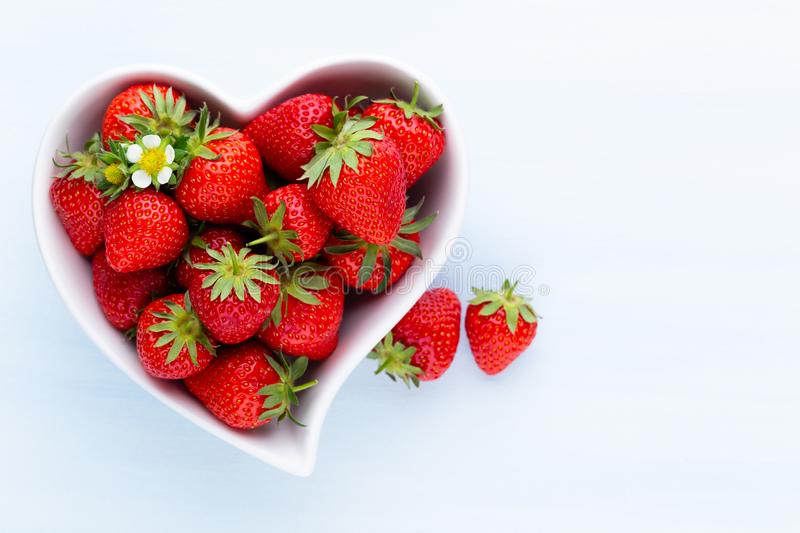 Strawberry heart. Fresh strawberries in plate on white wooden table. Top view, copy space royalty free stock photography