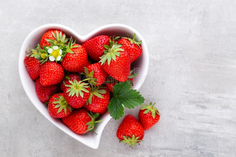 Strawberry heart. Fresh strawberries in plate on white wooden table. Top view, copy space stock photo