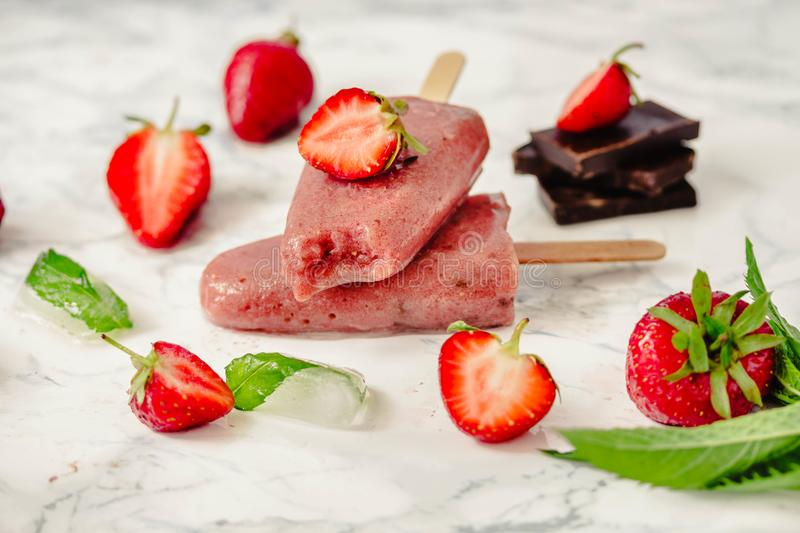 Strawberry ice cream with a banana and chocolate on a stick. Sum royalty free stock images
