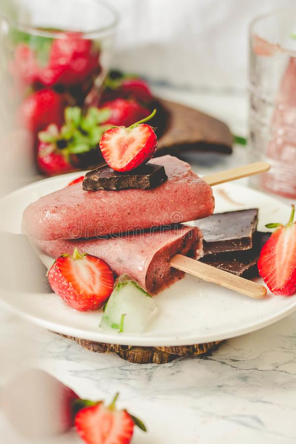 Strawberry ice cream with a banana and chocolate on a stick. Ton royalty free stock images