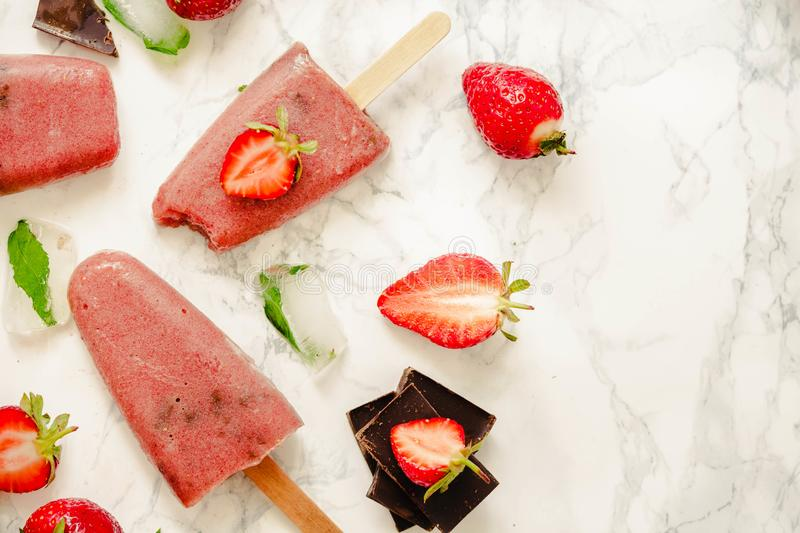 Strawberry ice cream with a banana and chocolate on a stick. Sum royalty free stock photos