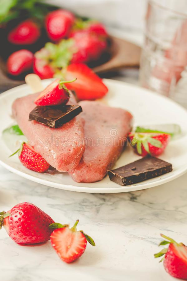 Strawberry ice cream with a banana and chocolate on a stick. Ton royalty free stock photography