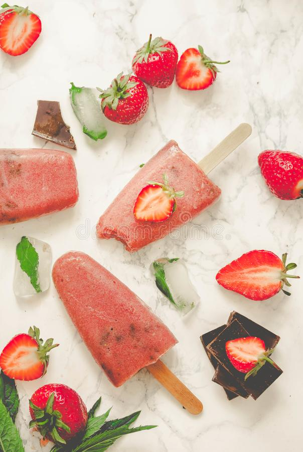 Strawberry ice cream with a banana and chocolate on a stick. Ton stock photography