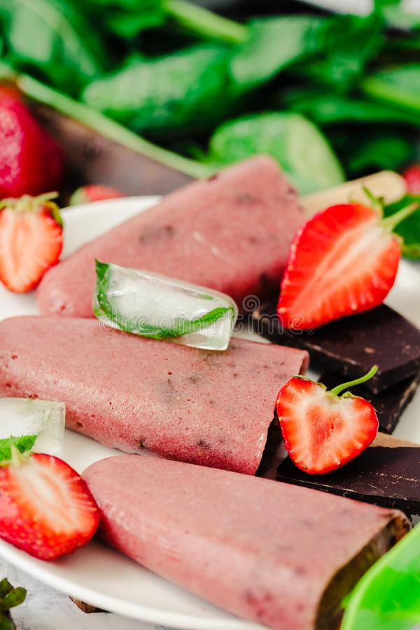 Strawberry ice cream with chocolate popsicles. Raw dessert. Mint royalty free stock images
