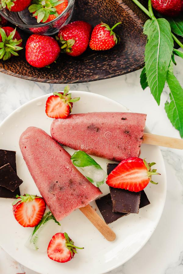 Strawberry ice cream with chocolate popsicles. Raw dessert. Mint royalty free stock image