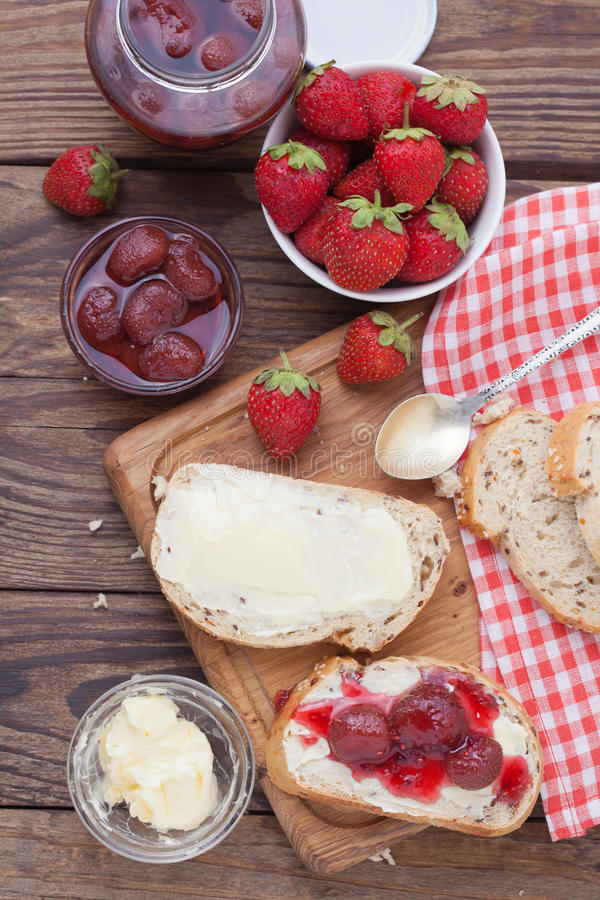 Strawberry jam, butter and bread on wooden table. stock images