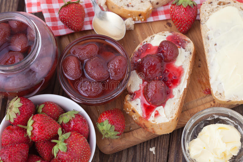Strawberry jam, butter and bread on wooden table. stock photo