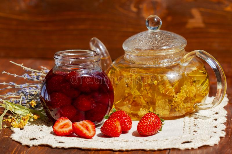 Strawberry jam in jar with fresh strawberries and teapot linden lavender tea and flowers on wooden background. Fresh royalty free stock photography