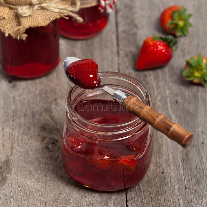 Strawberry Jam. On old wooden background. Selective focus royalty free stock photo