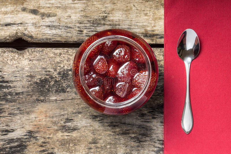 Strawberry jam with teaspoon served on wood background royalty free stock image