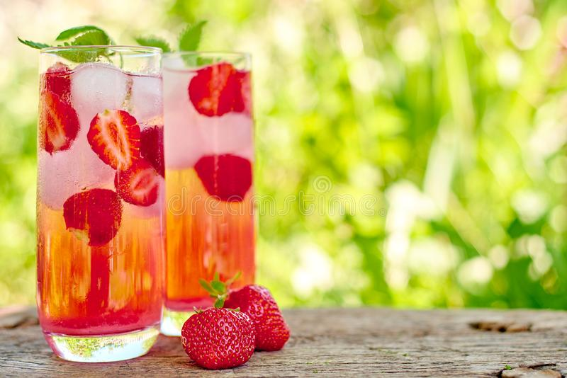 Strawberry lemonade, cocktail with ice and mint in glasses green background outdoors. stock image