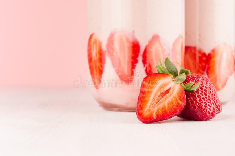 Strawberry milkshake in jar with slices ripe berry closeup, detail on gentle pastel pink and white background, copy space. stock photography